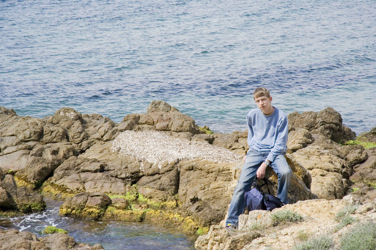 Portrait Of Young Man Sitting On Rocks Against Lake