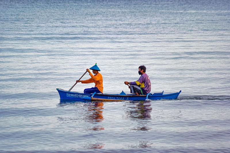 Men sitting on boat in sea