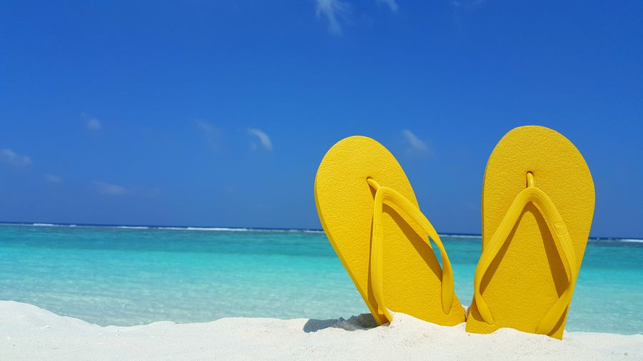 Close-Up Of Yellow Slippers Against Sea At Beach