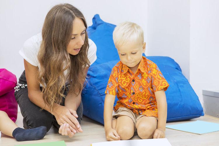 Mid adult teacher teaching student while sitting on floor against bean bag at school