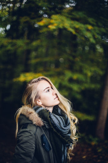 Young woman looking away while standing in forest