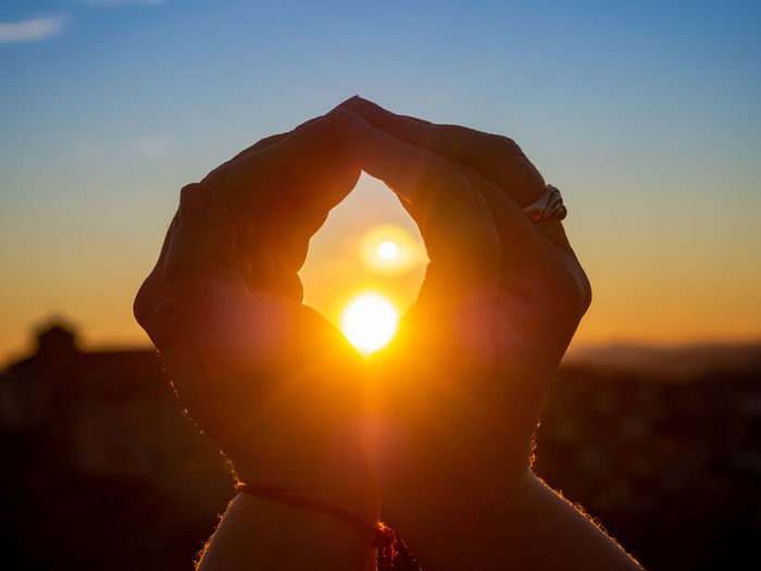 Close-up of woman hand against sun during sunset