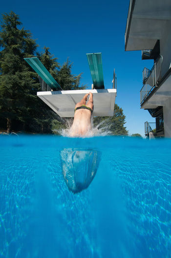 Over-Under Image Of A Springboard Diver Entering Water 20s Athlete Copy Space Diving Entering Jump Springboard Diver Sunlight Swiming Under Water Water Sport Blue Caucasian Dive Outdoors Splash Splashing Spring Board Summer Swimming Pool Underwater Unusual Angle Vertical Water Young Women