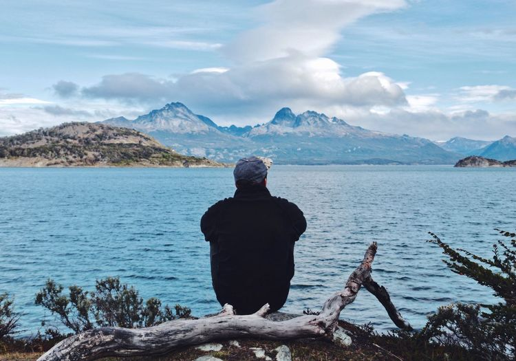 Rear View Of Man Sitting At Lakeshore Against Cloudy Sky