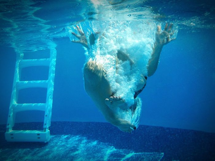 Underwater view of person jumping into swimming pool
