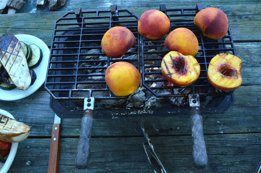 Peach halves grilling on top of a small tabletop Hibachi grill on picnic table outdoors Abundance Food Food And Drink Fresh Produce Freshness Grilled Grilled Fruit Grilled Peaches Group Of Objects Healthy Eating Healthy Food Healthy Lifestyle Hibachi Grill No People Peach Peaches