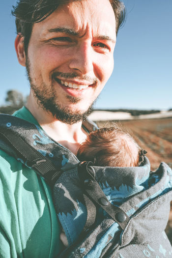 Portrait of smiling man with baby standing outdoors