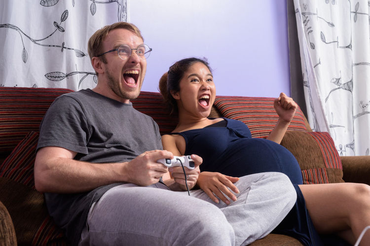 Excited couple playing game at home