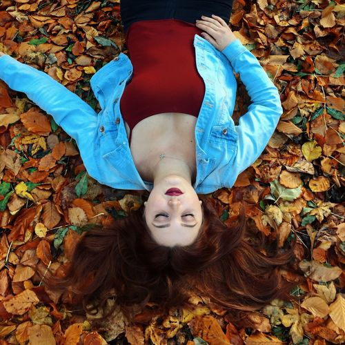 High Angle View Of Young Woman Lying Down On Autumn Leaves