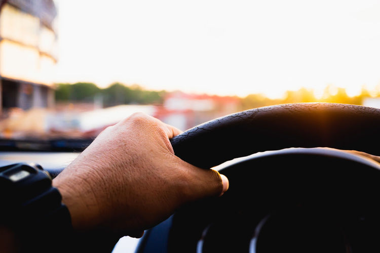 Close-up of hand holding car against sky during sunset