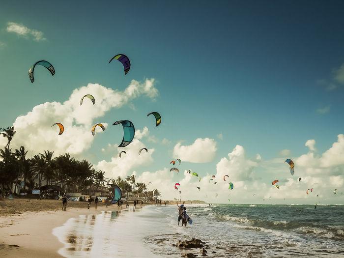 People kiteboarding at beach against sky