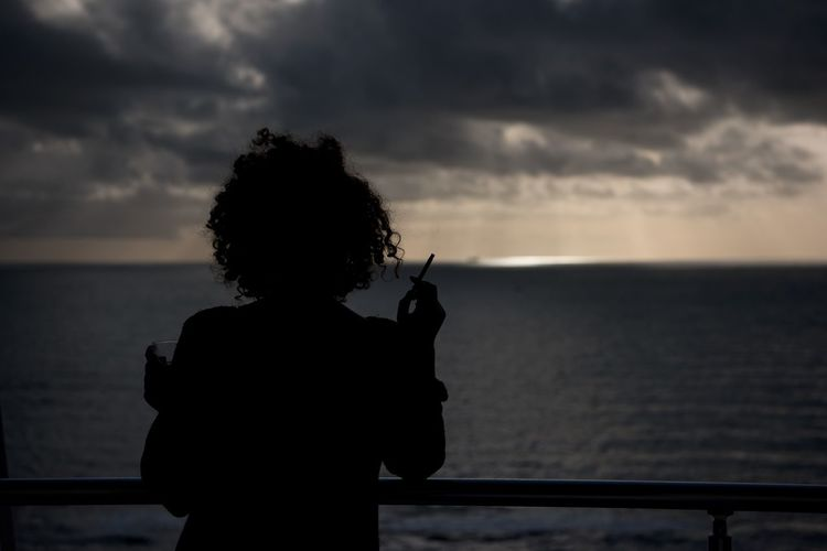 Silhouette Woman Smoking Cigarette Against Sea At Dusk