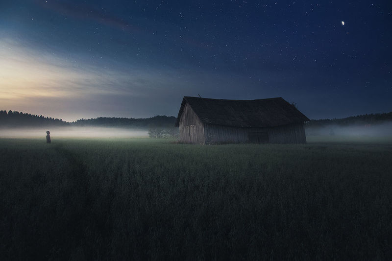 Person standing on field by barn against sky during foggy weather at night