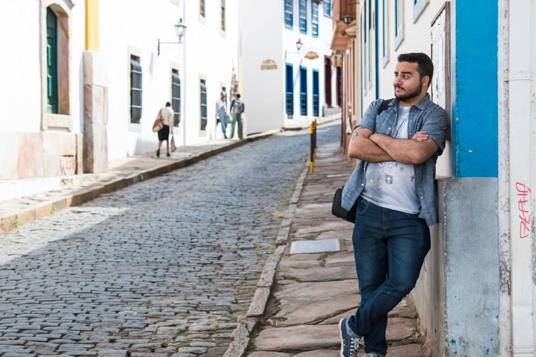 Young man leaning on wall by cobbled street in town