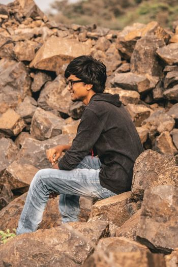 Side view of young man on rock
