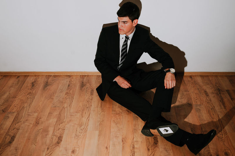 Man with card sitting on floor against wall