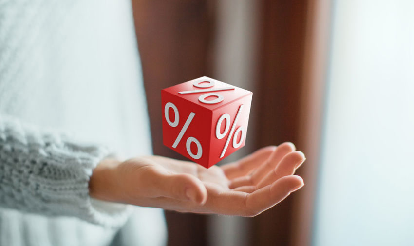 Digital composite image of man with percentage sign on cube icon