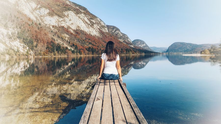 Rear view of woman sitting on pier over lake against mountains