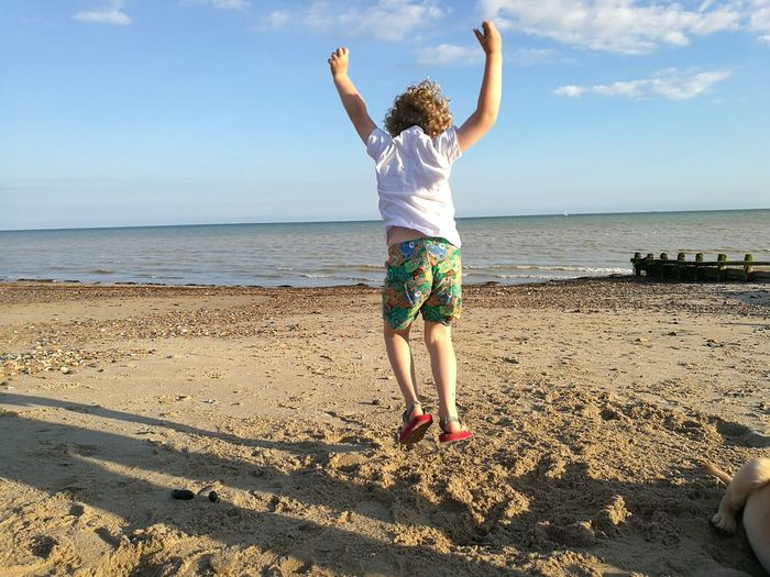 Rear View Of Boy Jumping At Beach Against Sky