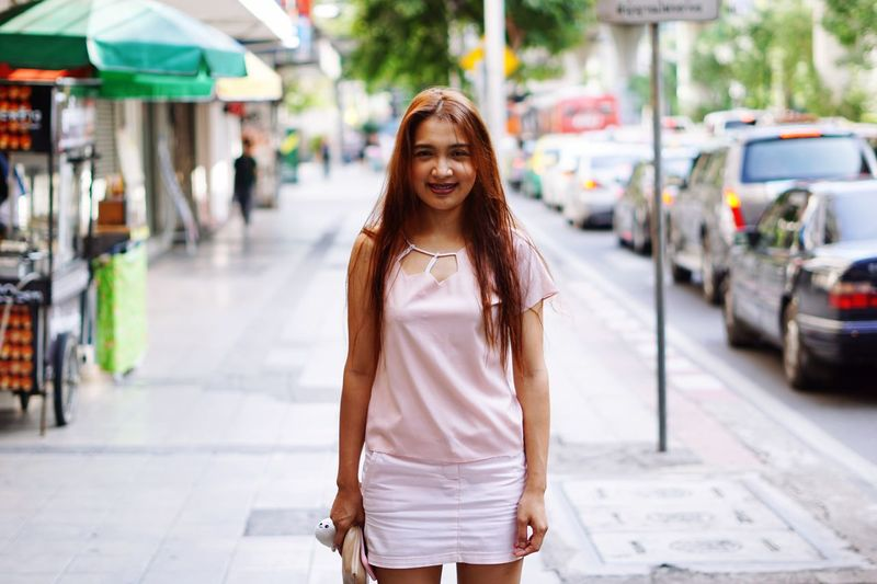 Portrait of young woman standing on sidewalk in city