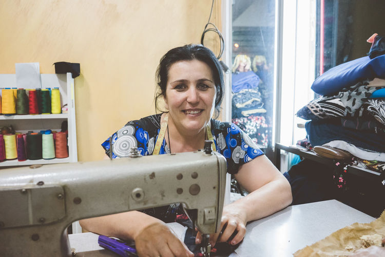 Portrait of smiling woman sewing cloth on machine