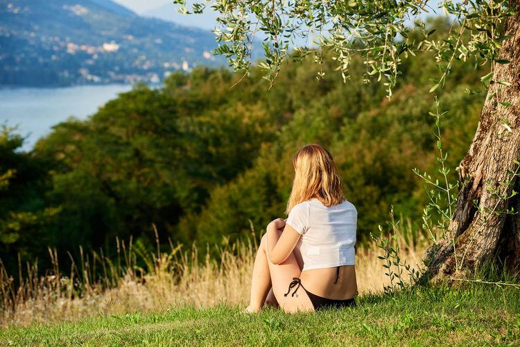 Woman in bikini bottom sitting on grass