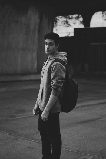 Portrait of young man standing on footpath in city