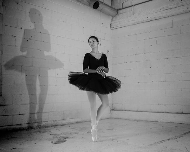 Ballerina Performing Ballet Dance Against Wall