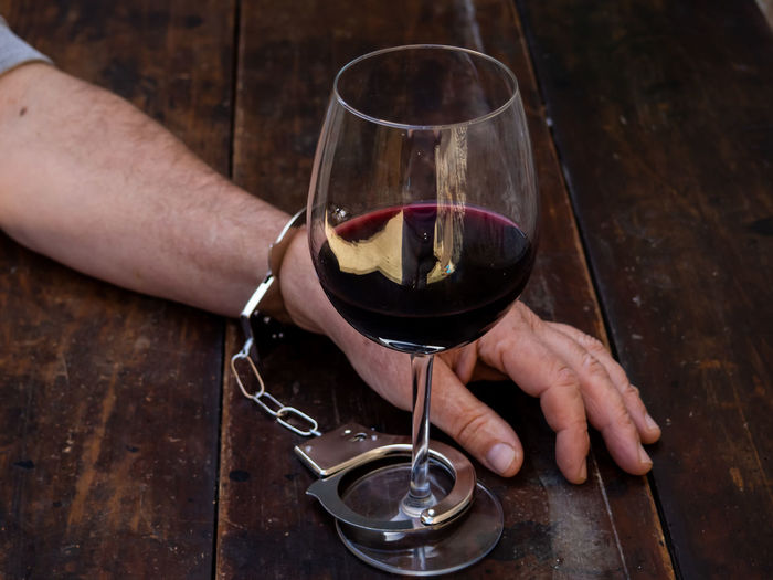 Midsection of man holding wine glass on table