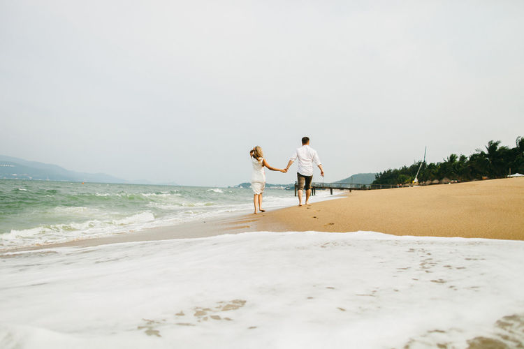 Rear view of couple walking on beach against clear sky