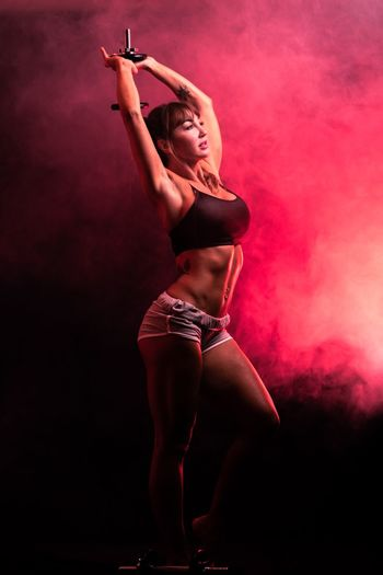 Woman exercising with dumbbell in artificial fog