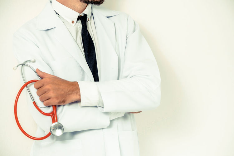 Midsection of doctor showing thumbs up while standing on white background