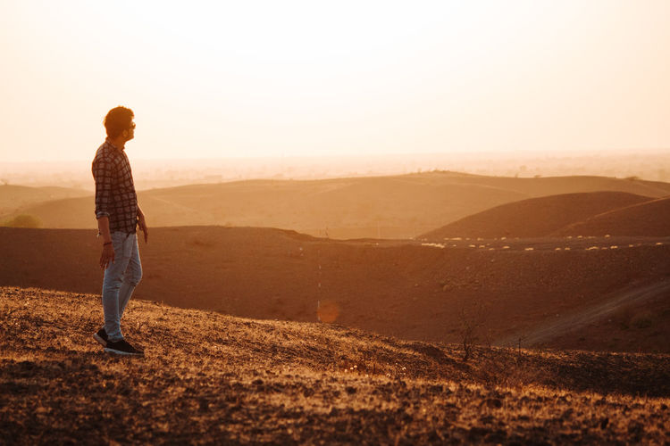 One Person Sky Standing Full Length Environment Landscape Scenics - Nature Leisure Activity Beauty In Nature Lifestyles Land Nature Real People Tranquility Tranquil Scene Sunset Non-urban Scene Casual Clothing Side View Outdoors Looking At View