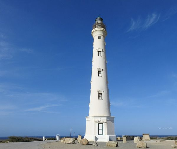 Low angle view of lighthouse by building against blue sky