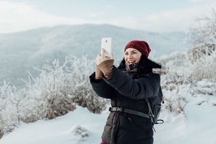 Smiling woman in warm taking selfie while standing on snowcapped mountain