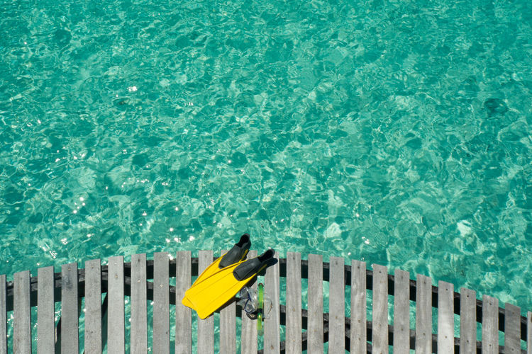 High angle view of snorkeling flippers and swimming goggles on pier over sea