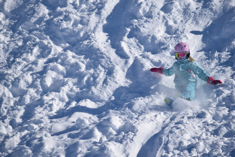 High angle view of girl playing on snow covered field