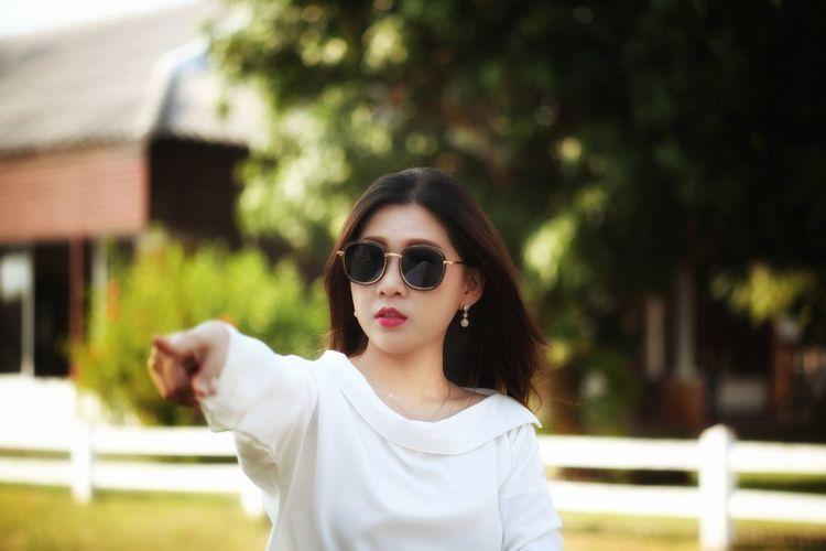 Woman wearing sunglasses gesturing outdoors