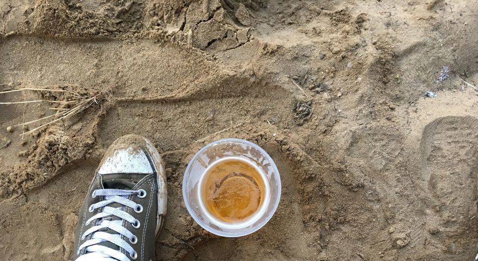 Low Section Of Person By Beer Glass On Sand At Beach