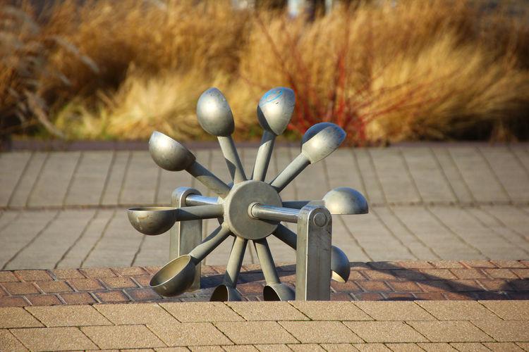 Metallic water wheel on footpath