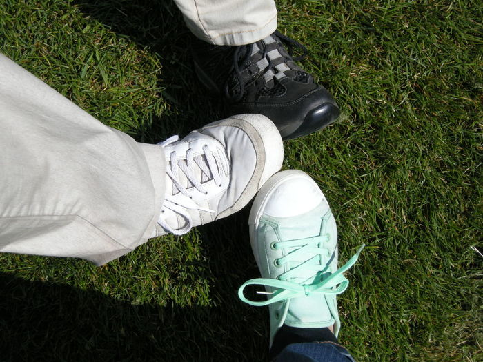 Low Section Of Friends Wearing Shoes On Grassy Field
