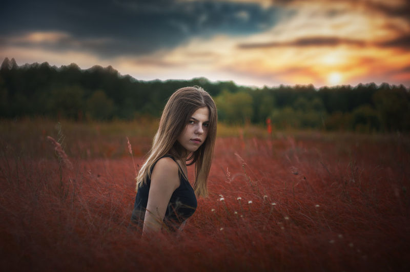 Portrait of woman on field against sky during sunset