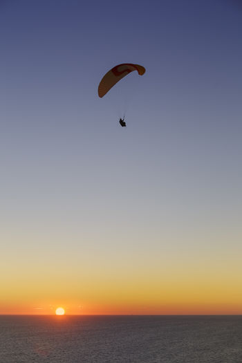 A man riding a paramotor watches the sunset over the sea in northern Denmark Sky Adventure Extreme Sports Sport Sunset Parachute Paragliding Unrecognizable Person Mid-air Real People Sea Leisure Activity Beauty In Nature Horizon Over Water Water Horizon Flying Freedom Scenics - Nature One Person Outdoors Paragliding Sunset, Verrical Denmark