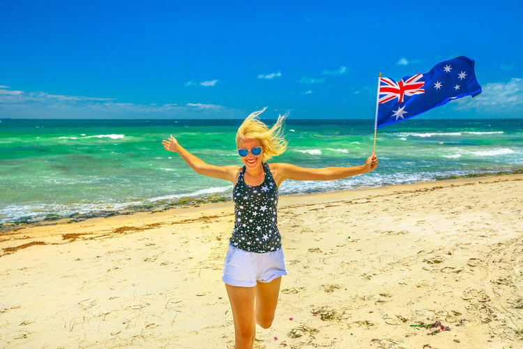 Woman holding australian flag running at beach