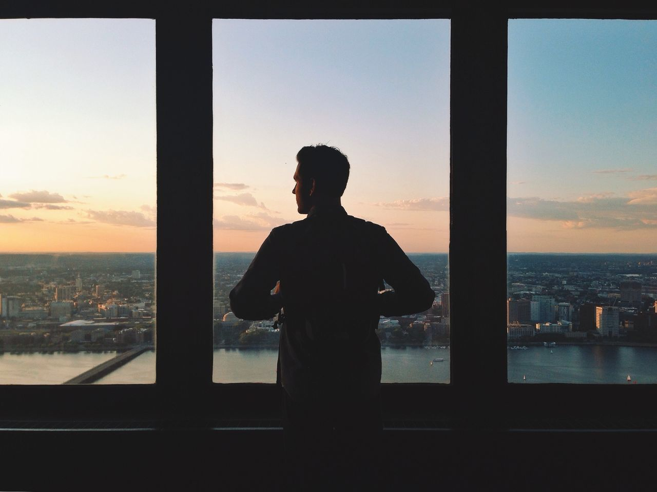 Rear view of man standing by window looking at city during sunset