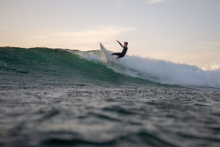 Sky One Person Motion Sport Leisure Activity Sea Lifestyles Water Wave Nature Sunset Skill  Beauty In Nature Cloud - Sky Men Real People Surfing Adventure Human Arm Freedom Outdoors
