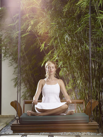 Full length of woman meditating while sitting on swing