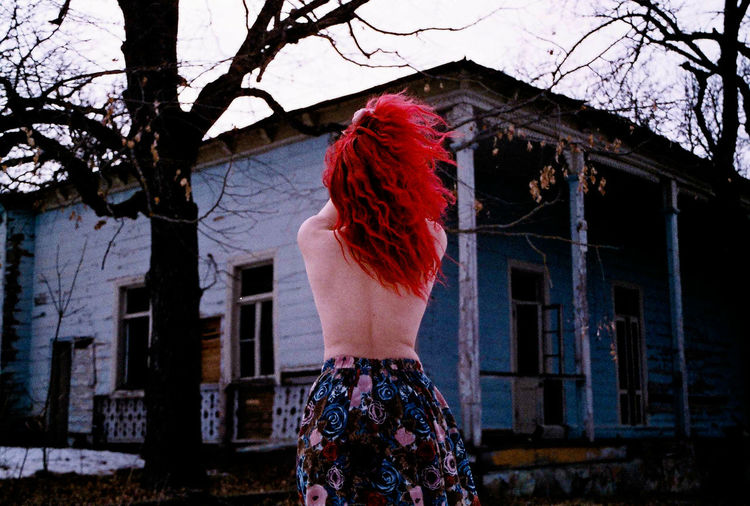 Rear View Of Shirtless Woman Standing Outdoors