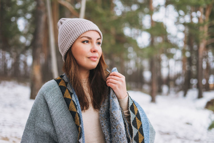 Portrait of young brunette beautiful woman in hat and grey poncho in the winter forest