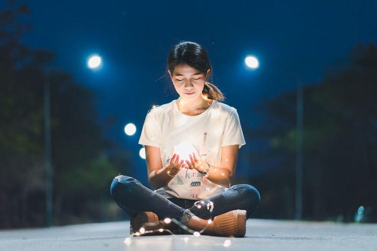 Young woman sitting on illuminated holding camera at night